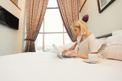 Happy woman sitting on bed in the hotel room Stock Photo