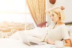 Happy woman sitting on bed in the hotel room Stock Images