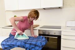 Happy woman or housewife ironing shirt at home kitchen using iro Royalty Free Stock Photo