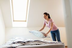 Happy woman or housewife making bed at home. Household, housework and cleaning concept - happy woman or housewife making bed at home Stock Images