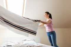 Happy woman or housewife making bed at home. Household, housework and cleaning concept - happy woman or housewife with towel making bed at home Stock Photography