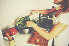 Happy woman housewife preparing salad in the kitchen Stock Photography