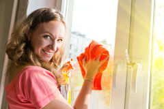 Happy woman housewife washes a window Royalty Free Stock Photo