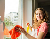 Happy woman housewife washes a window Royalty Free Stock Photos