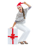 Happy woman in hristmas hat sitting on big christmas present box Stock Images