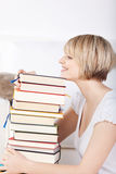 Happy woman with a huge stack of books Stock Image