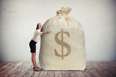 Happy woman hugging a big bag of money Stock Photography