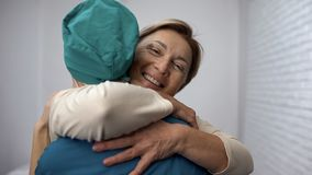 Happy woman hugging doctor, good test results, recovery and remission, gratitude