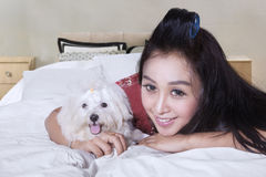 Happy woman hugging dog on bed. Pretty young model with long hair, lying on bed while hugging a maltese dog and smiling at the camera Royalty Free Stock Photos