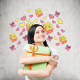 A happy woman is hugging a green gift box. Gift and heart icons are drawn on the concrete wall. A happy brunette woman is hugging a green gift box. Gift and Stock Photo