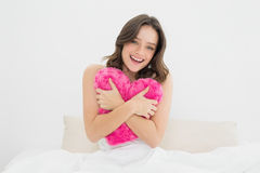 Happy woman hugging heart shaped pillow in bed Royalty Free Stock Images