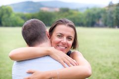 Happy woman hugging her boyfriend outdoor in a park Stock Photo