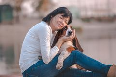 Happy woman hugging her dog Basset Hound. Portrait of beautiful young woman sitting next to the river and hugging her dog Basset Hound. Happy woman likes to stock images