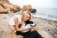 Happy woman hugging her dog and smiling on the beach Stock Photo