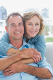 Happy woman hugging her husband on the couch from behind Stock Photography