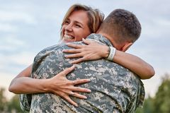 Happy woman hugging his husband came back from army. stock photography