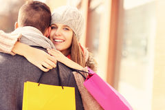 Happy woman hugging a man while shopping Stock Photography