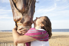Happy. Woman hugging palm tree Royalty Free Stock Photos