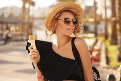 Happy woman with ice cream wearing sunglasses and beach hat having summer fun during travel holidays vacation stock images