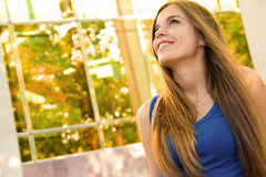 Happy woman indoors. Happy young woman indoors with long hair, window and leafy trees in background stock photography