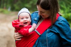 Happy woman with infant baby in forest having fun. Woman and her infant baby outdoors with Baby carrier slings Stock Images