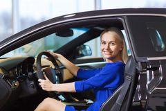 Happy woman inside car in auto show or salon Royalty Free Stock Photos