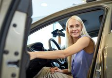 Happy woman inside car in auto show or salon Royalty Free Stock Image