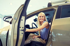 Happy woman inside car in auto show or salon Stock Photos