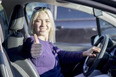 Happy woman inside a car driving in the street and gesturing thu royalty free stock photo