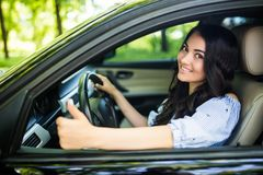 Happy brunette woman inside a car driving in the street and gesturing thumb up royalty free stock image