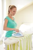 Happy woman with iron and ironing board at home Royalty Free Stock Photos