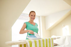 Happy woman with iron and ironing board at home Stock Photo