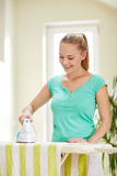 Happy woman with iron and ironing board at home Royalty Free Stock Photography