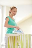 Happy woman with iron and ironing board at home Stock Photos