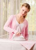 Happy woman ironing clothes. Happy young beautiful woman ironing clean clothes stock image