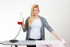 Happy woman ironing creased clothes Stock Images