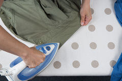 Happy woman Ironing man's shirt with electric Iron Royalty Free Stock Image