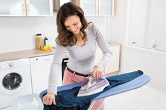 Happy Woman Ironing Trousers Royalty Free Stock Images