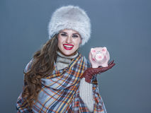 Happy woman isolated on cold blue background showing piggy bank Royalty Free Stock Photography
