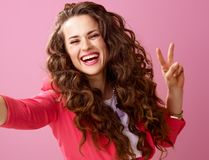 Happy woman isolated on pink taking selfie and showing victory Royalty Free Stock Photography