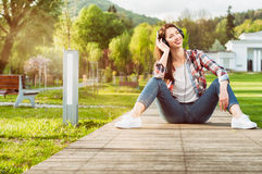 Happy woman in jeans and plaid shirt enjoying music. Smiling and relaxing outside in the nature as carefree concept Royalty Free Stock Images