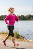 Happy woman jogger training in the park Royalty Free Stock Photos
