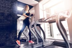 Happy women jogging on a treadmill for health. stock image