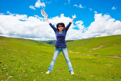 Happy woman jump. Over the grassland into the sky Stock Photo