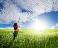 Happy woman jump in grass fields and blue sky Royalty Free Stock Photo