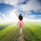Happy woman jump in green rice fields and  blue sk Stock Image