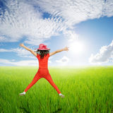 Happy woman jump in green rice fields and clouds sky Royalty Free Stock Images