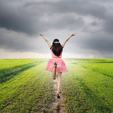 Happy woman jump in green rice fields and rainclouds Stock Photography