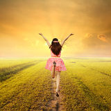 Happy woman jump in green rice fields and sunset Stock Photography