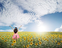 Happy woman jump in sunflower fields and blue sky Stock Image